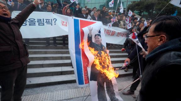 Protesters set a portrait of North Korean leader Kim Jong Un on fire Monday.