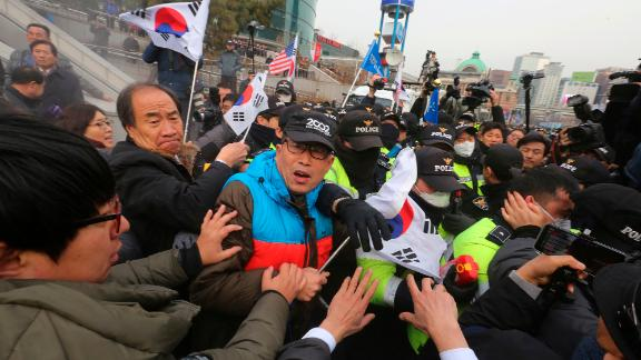 South Korean protesters struggle with police officers as police use fire extinguishers during a rally Monday.