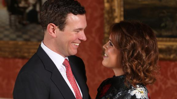 LONDON, ENGLAND -JANUARY 22: Princess Eugenie and Jack Brooksbank in the Picture Gallery at Buckingham Palace after they announced their engagement. Princess Eugenie wears a dress by Erdem, shoes by Jimmy Choo and a ring containing a padparadscha sapphire surrounded by diamonds on January 22, 2018 in London, England..  They are to marry at St George