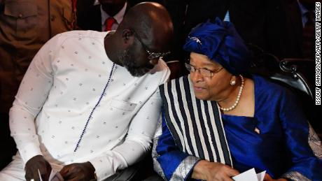 Liberia's president-elect and former football star George Weah (L) listens to the country's outgoing president Ellen Johnson Sirleaf during a church service at the centennial memorial pavilion in Monrovia on January 21, 2018, the eve of Weah's inauguration. Ellen Johnson Sirleaf, who shared the 2011 Nobel Peace Prize as a champion of women's rights, is stepping down after making history as Africa's first elected female president in Liberia.
