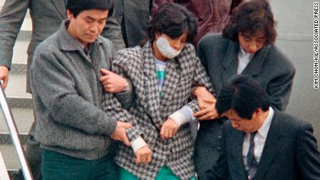 Agents escort Kim Hyon Hui, with her mouth taped shut, as she arrives in Seoul, South Korea, Dec. 15, 1987, from Bahrain.