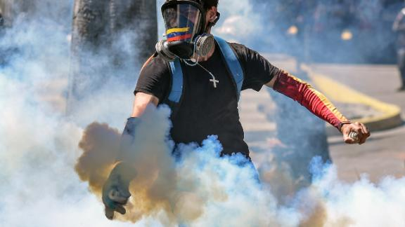 A demonstrator throws a tear gas canister back at the riot police during clashes in Caracas on January 22, 2018 which erupted during a protest to condemn the death of dissident former police officer Oscar Perez - gunned down in a bloody police operation on February 16.  Perez, whose body was buried by the government on January 21 against his family's wishes, was Venezuela's most wanted man since June when he flew a stolen police helicopter over Caracas dropping grenades on the Supreme Court and opening fire on the Interior Ministry.  / AFP PHOTO / Juan BARRETO        (Photo credit should read JUAN BARRETO/AFP/Getty Images)