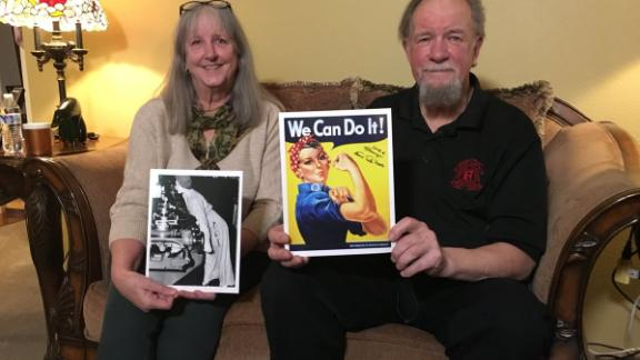 Naomi Parker Fraley's daughter-in-law and son hold up a photograph of her taken during World War II and the poster it inspired.
