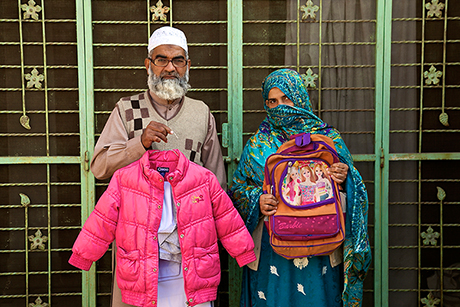 The parents of Zainab Ansari -- Muhammad Amin Ansari, 48, and Nusrat Amin, 45 -- hold  their daughter's school uniform, jacket and Barbie schoolbag.