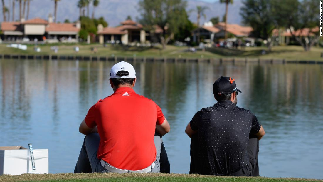 <strong>Taking a break: </strong>Spain's Jon Rahm (left) and Adam Hadwin of Canada wait on the sixth tee during the final round of the CareerBuilder Challenge. Rahm went on to win a four-hole playoff against Andrew Landry for his second PGA Tour title. He also rose to world No. 2