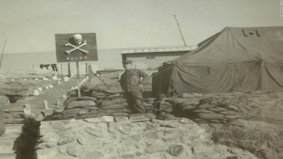 A photo from 1970 shows Air Force Sergeant Yang Dong-soo standing in front of a skull and crossbones sign on the island of Silmido. Yang was assigned to train members of the assassination squad when he was 21 years old. He says the skull and cross bones were real human bones.