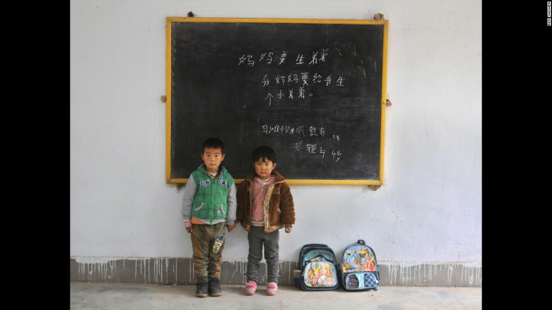 "Zang Yixuan, 5, and his brother Zang Yaxuan, 4, at Ma Tan elementary school. Their messages read: ""Mommy wants to have another boy."" ""My mommy wants to give me a little brother."""