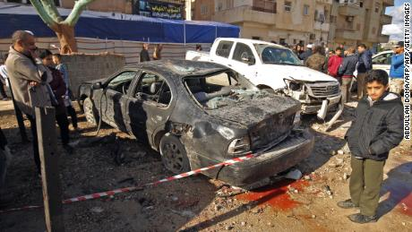 Security officials inspect the destruction left behind after two explosions near a mosque in Benghazi on January 24, 2018.
