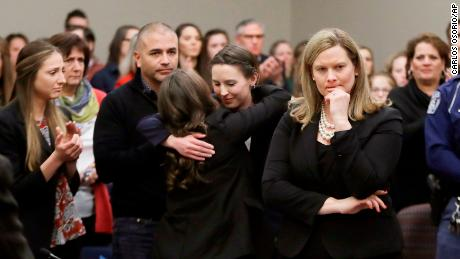 Assistant Attorney General Angela Povilaitis stands in court after former gymnast Rachael Denhollander, center, is hugged following her victim impact statement in the Larry Nassar sentencing proceedings.