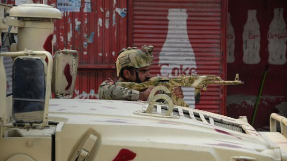 An Afghan army soldier takes a position Wednesday near the Save the Children office in Jalalabad.