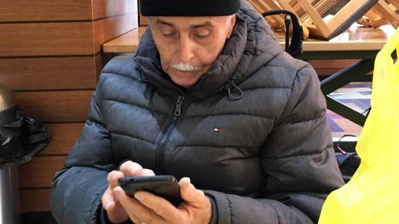 Bienvenido Ramirez checks his smartphone for news from home.