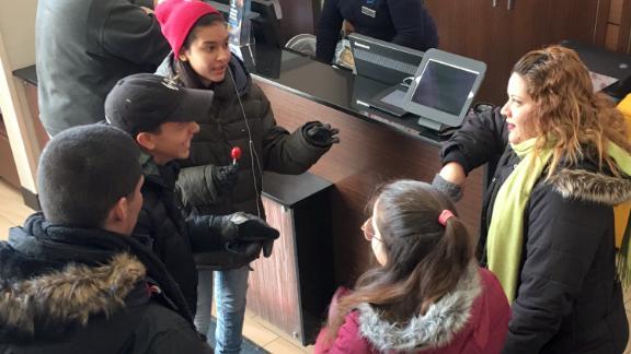 Liz Cruz, right, husband Elvin Gonzalez and her children in the lobby of a Manhattan hotel in January.