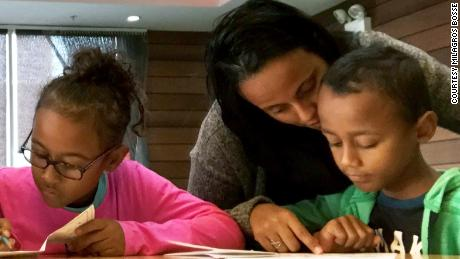 Milagros Bosse helps her children with homework in the lobby of their New York City hotel.