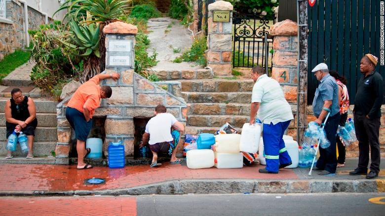 People collect water from pipes fed by an underground spring in St. James, a Cape Town suburb.