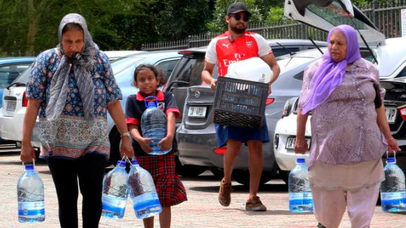 People carry water collected from a natural spring earlier this week in Cape Town.