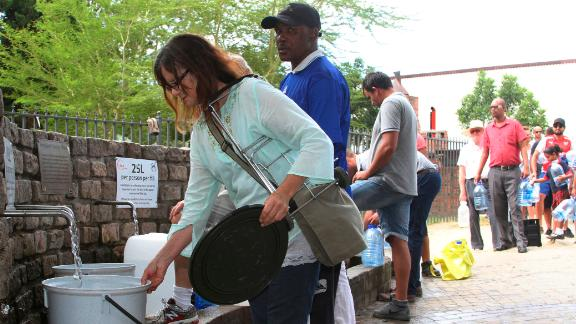 "People queue to collect water from a natural spring in Cape Town, South Africa, Monday, Jan 22, 2018 as the city suffers from one of the worst droughts in recent history. Officials are looking to combat the drought, saying it was looking more likely that it will have to turn off most taps on ""Day Zero,"" or April 21 stating that 60 percent of residents are ""callously"" using more than the current limit and that the city will fine households that use too much water. (AP Photo/Anwa Essop)"