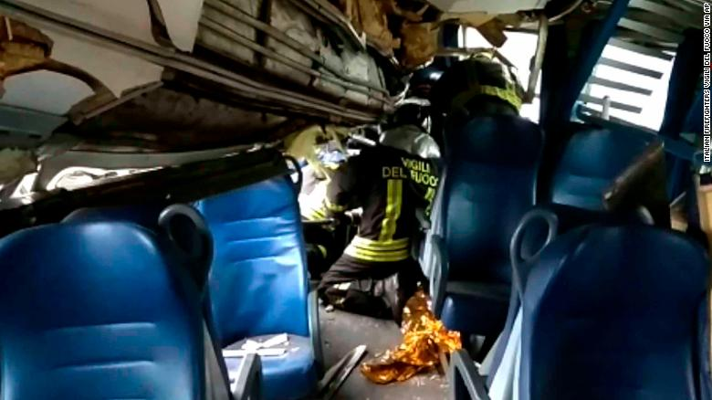 Rescuers inside one of the train carriages try to help a passenger Thursday.