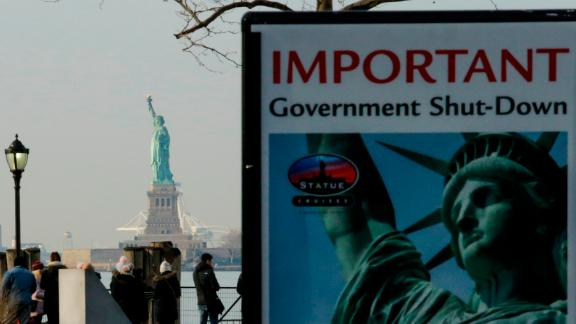 NEW YORK, NY - JANUARY 21: A Shutdown placard is seen at the entrance of the Liberty State ferry terminal as people look on in Battery Park on January 21, 2018 in New York City. The iconic landmark remains closed as part of the US government shutdown now entering its second full day after coming into effect at midnight on Friday after senators failed to pass a new federal spending bill. (Photo by Eduardo Munoz Alvarez/Getty Images)