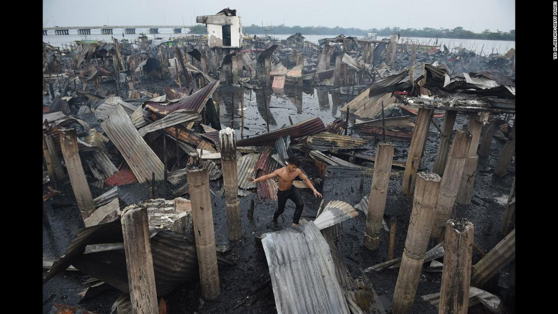 "A resident walks on a galvanized roof sheet and destroyed homes after a fire at an informal settlers' area in Cavite province, Philippines, on Wednesday, January 24. ""About 400 families lost their homes,"" <a href=""http://newsinfo.inquirer.net/963218/400-families-in-cavite-lose-homes-to-fire"" target=""_blank"">according to the Philippine Daily Inquirer</a>."