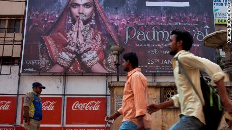 "Policemen guard as people arrive to watch Bollywood film ""Padmaavat"" outside a movie theatre in Hyderabad, India, Thursday, Jan. 25, 2018. The film, based on a 16th century Sufi epic poem, has sparked protests and anger due to allegations of distorting history and is being screened from today. (AP Photo/Mahesh Kumar A.)"