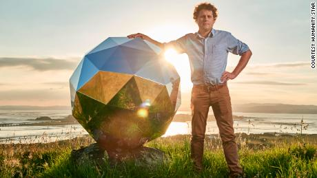 Peter Beck, creater of The Humanity Star, poses next to the satellite.