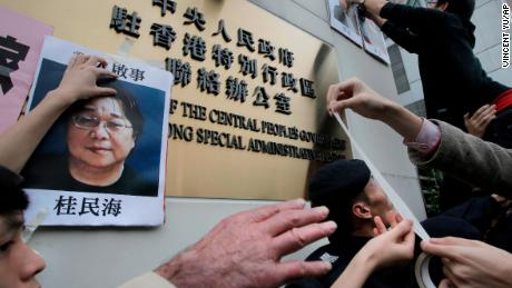 Protesters stick photos of missing publisher Gui Minhai on the outside of a Chinese government building in Hong Kong in July 2016. Gui first disappeared in 2015.