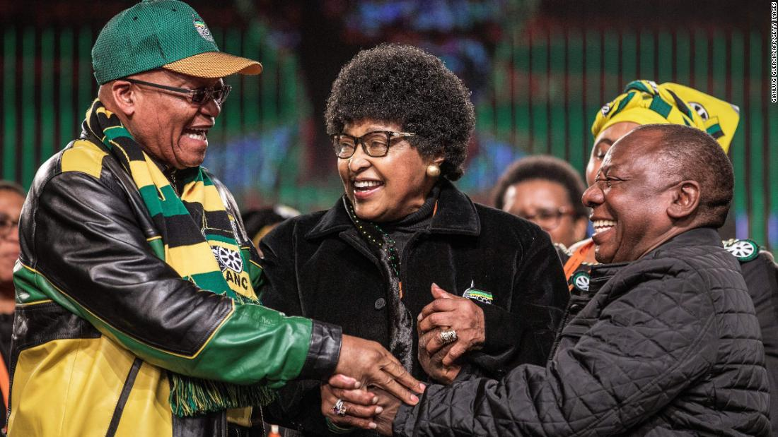 "Madikizela-Mandela joins the hands of South African President <a href=""http://www.cnn.com/2018/02/08/africa/gallery/jacob-zuma-career/index.html"" target=""_blank"">Jacob Zuma, </a>left, and Deputy President Cyril Ramaphosa during an African National Congress policy conference in 2017."