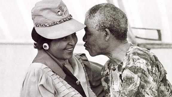 Mandela leans in to kiss his wife at a rally in March 1990.