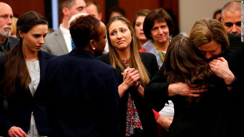 Rachael Denhollander (left),   Kyle Stephens (center) and others in the courtroom gather and embrace after Larry Nassar was sentenced to up to 175 years in prison.