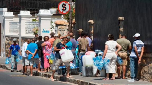 South Africa Western Cape Province. People queue to collect drinking water from pipes fed by an underground spring, in St. James, about 25km from the city centre on 26 January, 2017.  Low rainfall in the previous two rainy season means that the Western Cape Province is in the grips of the worst drought in a century, with taps in the Cape Town metropole estimated to run dry in April 2018, unless rains come earlier than they usually do. Dams in this area are 30% full, with the last 10% not accessable.