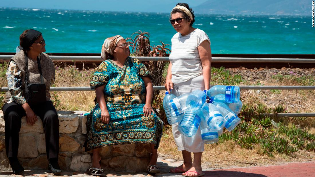 "Women talk before collecting drinking water from pipes fed by an underground spring, in St. James, outside central Cape Town. April 16 has been dubbed ""Day Zero,"" when water taps are expected to run dry."