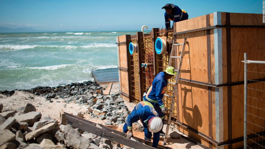 Workers set up a desalination unit on Strandfontein Beach.