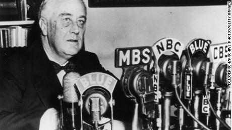 President Franklin D. Roosevelt seated in front of a number of television and radio station microphones, circa 1940s.