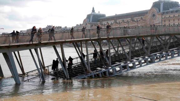 People examine the Seine river from the Leopold-Sedar-Senghor bridge in Paris on Friday.