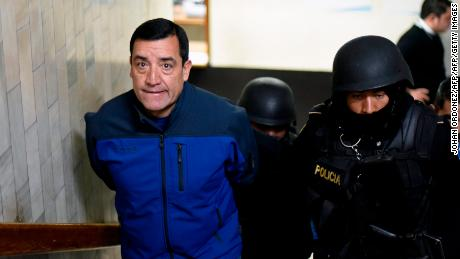 "Former Guatemalan Defense Minister Williams Mansilla (L) is escorted by police officers on arrival at a courtroom in Guatemala City after being arrested on January 26, 2018.   Mansilla, was arrested on Friday for having authorized the payment of an ""extraordinary bonus"" to Guatemalan President Jimmy Morales, the prosecution reported. / AFP PHOTO / JOHAN ORDONEZ        (Photo credit should read JOHAN ORDONEZ/AFP/Getty Images)"