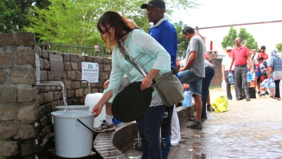 """People queue to collect water from a natural spring in Cape Town, South Africa, Monday, Jan 22, 2018 as the city suffers from one of the worst droughts in recent history. Officials are looking to combat the drought, saying it was looking more likely that it will have to turn off most taps on """"Day Zero,"""" or April 21 stating that 60 percent of residents are """"callously"""" using more than the current limit and that the city will fine households that use too much water. (AP Photo/Anwa Essop)"""