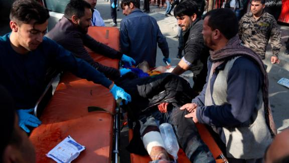 An injured man is moved to a stretcher outside a Kabul hospital following Saturday