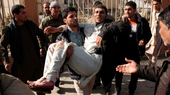An injured man is carried away from the site of a deadly suicide attack Saturday in Kabul.