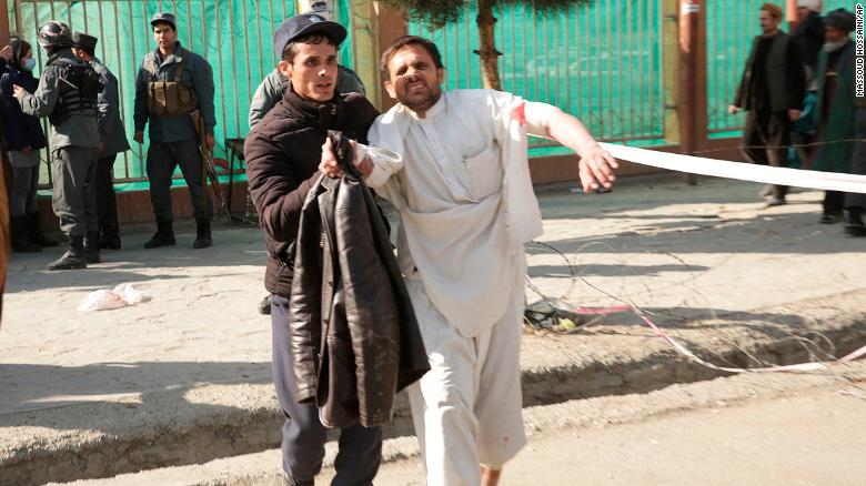 A wounded man is helped near the blast scene Saturday in Kabul.