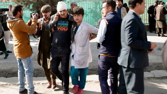 A wounded man is assisted at the site of an explosion in downtown Kabul, Afghanistan, Saturday, Jan. 27, 2018. The Interior Ministry says a suicide car bomb attack in Kabul has left dozens wounded. (AP Photo/Massoud Hossaini)