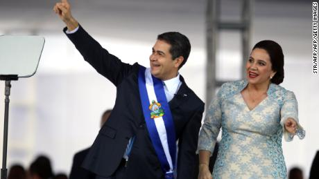 Reelected Honduran President Juan Orlando Hernandez (L) waves at the crowd wearing the presidental sash next to First Lady Ana García at the Tiburcio Carias Andino national stadium, in Tegucigalpa, on January 27, 2018 Hernandez begins his second presidential term as the opposition vowed mass protests over claims he fraudulently won November elections. / AFP PHOTO / STR        (Photo credit should read STR/AFP/Getty Images)