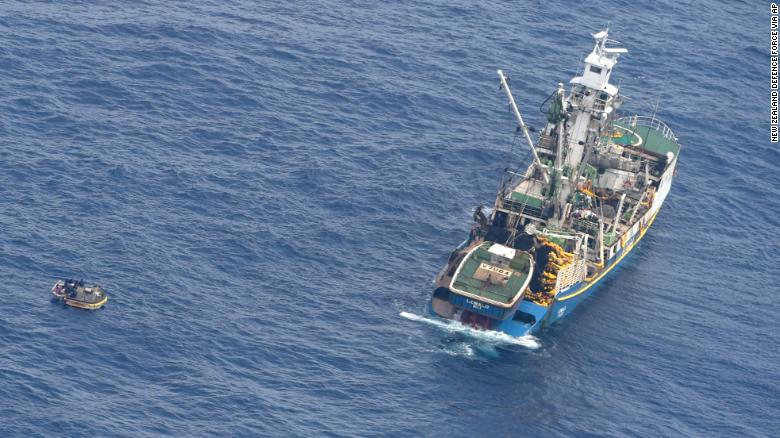 This photo released by the New Zealand defense force shows a wooden dinghy, left, carrying seven survivors from a missing ferry and a fishing boat in the Pacific Ocean on Sunday.