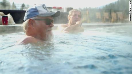 Two friends soak in Olympic-size pool fed by hot springs in Idaho City, Idaho.