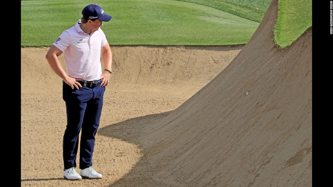 Paul Dunne looks at his ball, which was plugged deep in the face of a greenside bunker during the Omega Dubai Desert Classic on Friday, January 26.