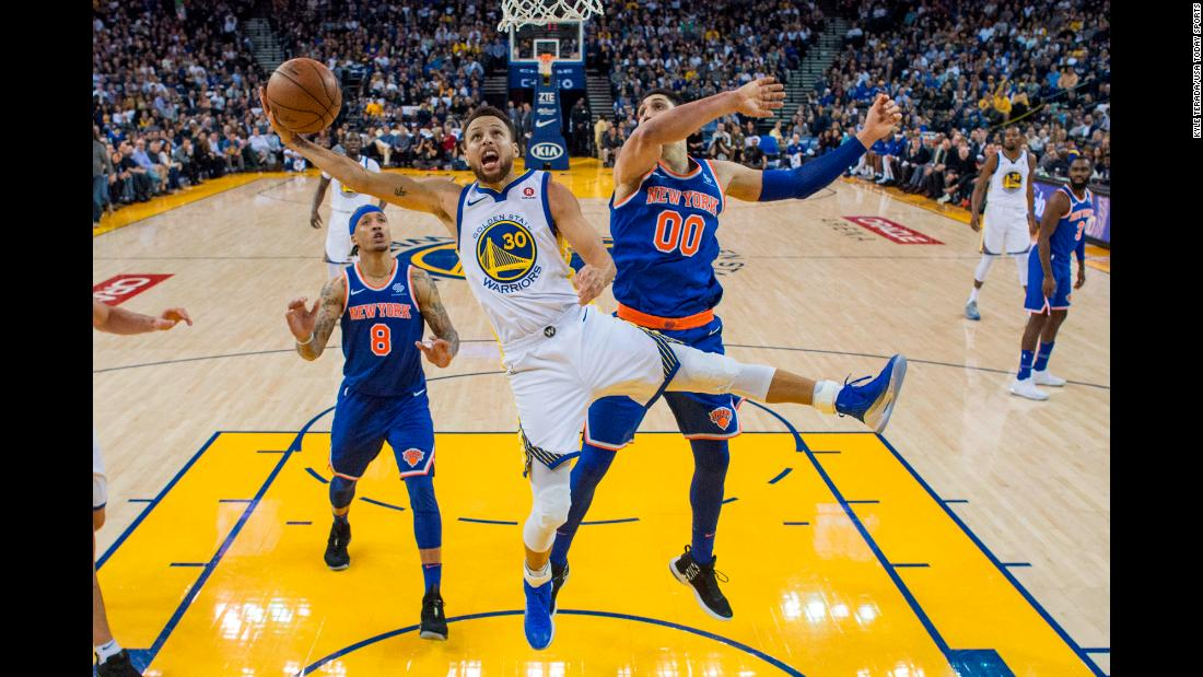 Golden State guard Stephen Curry avoids New York center Enes Kanter as he rises for a shot on Tuesday, January 23. Curry scored 32 points in the Warriors' 123-112 victory.