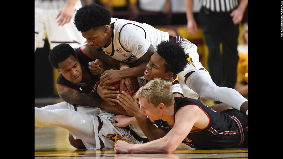 Players from Utah and Arizona State compete for a loose ball during a college basketball game in Tempe, Arizona, on Thursday, January 25.