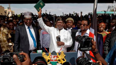 "Opposition leader Raila Odinga holds a bible aloft after swearing an oath during a mock ""swearing-in"" ceremony at Uhuru Park in downtown Nairobi, Kenya Tuesday, Jan. 30, 2018. Odinga was sworn-in as ""the people's president"" during a mock ""inauguration"", in protest of President Uhuru Kenyatta's new term following the divisive 2017 election, and despite the government's warning that the event would be considered treason. (AP Photo/Ben Curtis)"