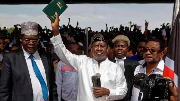"Opposition leader Raila Odinga holds a bible aloft after swearing an oath during a mock ""swearing-in"" ceremony at Uhuru Park in downtown Nairobi, Kenya Tuesday, Jan. 30, 2018. Odinga was sworn-in as ""the people"