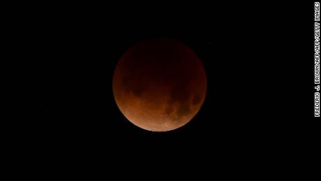 "A Super Blue Blood Moon hovers over Los Angeles, California in the early hours of January 31, 2018, during an event not seen since 1866 when three fairly common lunar happenings occur at the same time.  Stargazers across large swathes of the globe -- from the streets of Los Angeles to the slopes of a smouldering Philippine volcano -- had the chance to witness a rare ""super blue blood Moon"" Wednesday, when Earth's shadow bathed our satellite in a coppery hue.The celestial show is the result of the Sun, Earth, and Moon lining up perfectly for a lunar eclipse just as the Moon is near its closest orbit point to Earth, making it appear ""super"" large.  / AFP PHOTO / Frederic J. BrownFREDERIC J. BROWN/AFP/Getty Images"