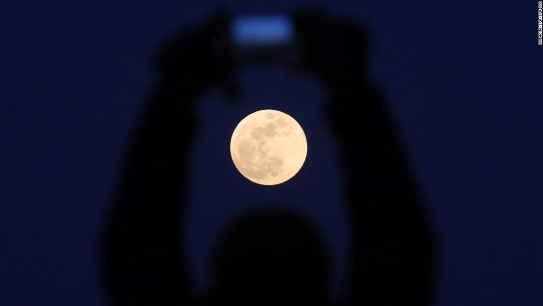 A man takes a photo of the supermoon rising in Beijing.